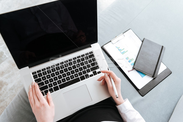 Cropped image of young business lady using laptop. Stock photo © deandrobot