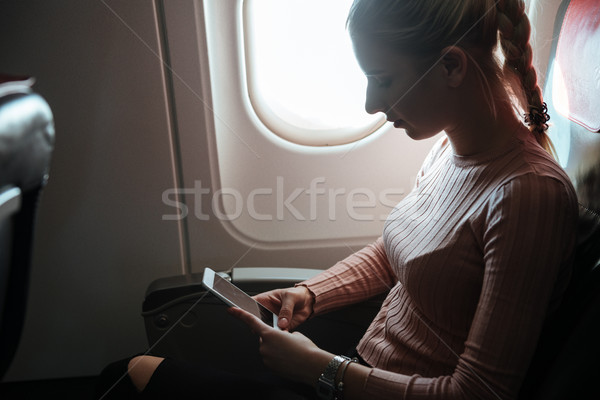 Side view of woman using phone in aircraft Stock photo © deandrobot