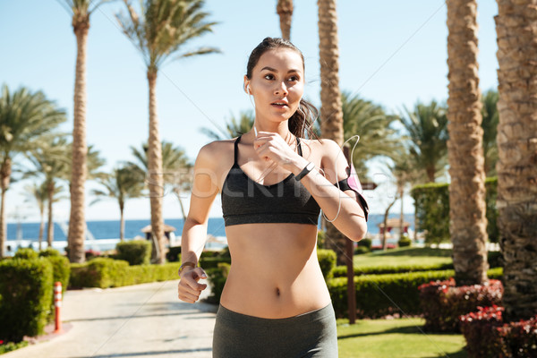 Fitness woman with earphones running in summer Stock photo © deandrobot