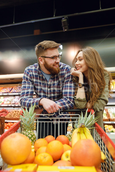Loving couple standing near the shopping trolley Stock photo © deandrobot
