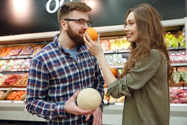 Mulher cheiro laranja homem supermercado mulheres Foto stock © deandrobot