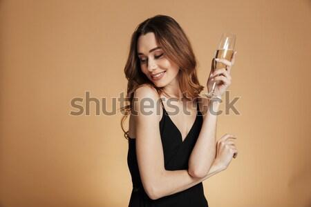 Gülen genç kadın kırmızı elbise ayakta içme şampanya Stok fotoğraf © deandrobot
