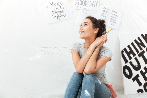 Dreaming young lady artist sitting on floor Stock photo © deandrobot