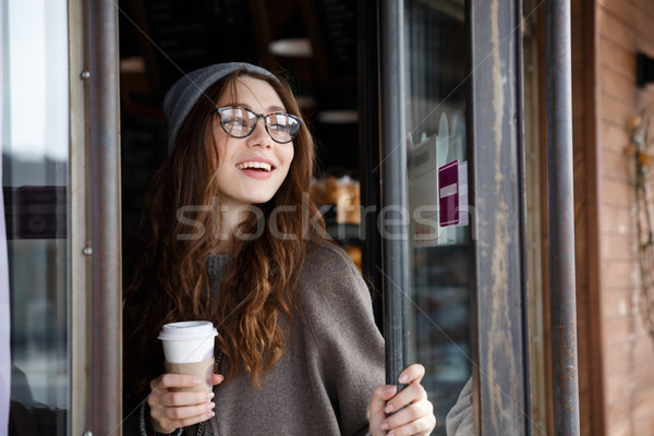 Cheerful lovely young woman drinking take away coffee Stock photo © deandrobot