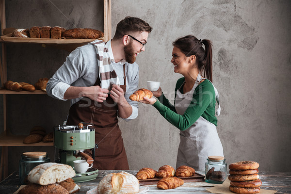 Happy loving couple bakers drinking coffee Stock photo © deandrobot