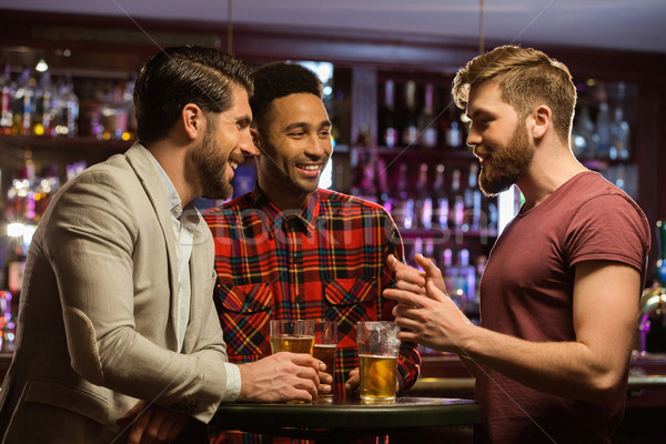 Young happy men drinking beer and talking in cafe Stock photo © deandrobot