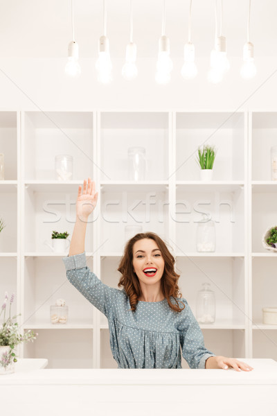 Happy young lady sitting in shop over shelf background Stock photo © deandrobot