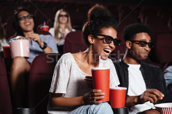 Happy young friends sitting in cinema watch film Stock photo © deandrobot