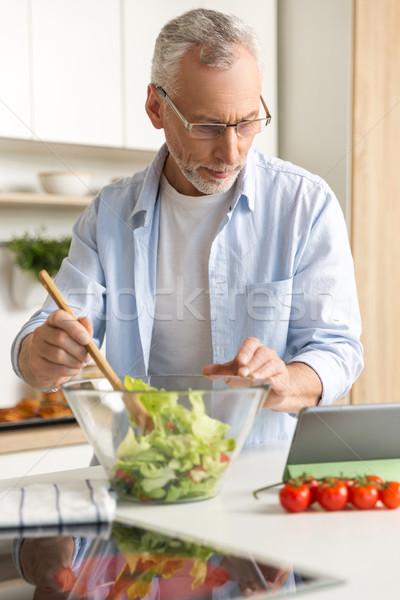Bonito concentrado homem maduro cozinhar salada comprimido Foto stock © deandrobot