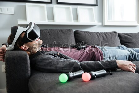 Happy man sitting at home play games with 3d glasses. Stock photo © deandrobot
