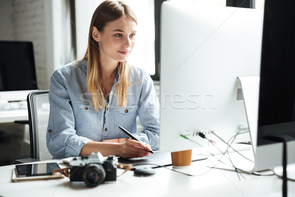 Cheerful young woman work in office using computer Stock photo © deandrobot