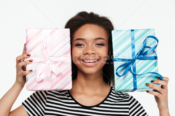 Happy afro american woman holding two present boxes Stock photo © deandrobot