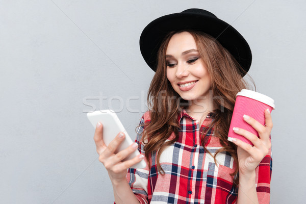 Portrait of a pretty casual woman in hat typing message Stock photo © deandrobot