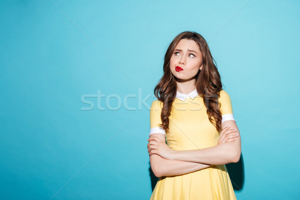 Portrait of a disappointed cute girl in dress standing Stock photo © deandrobot