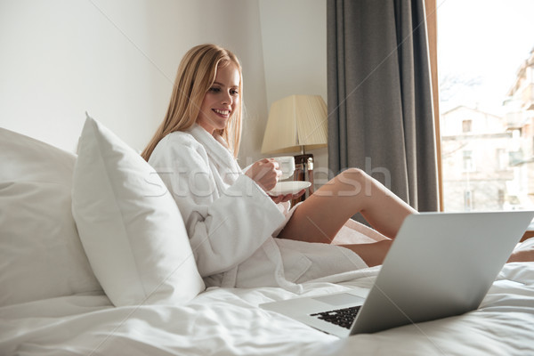 Smiling blonde woman in bathrobe holding cup of coffee Stock photo © deandrobot