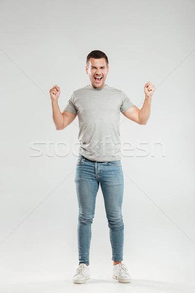 Izgatott fiatalember gyártmány nyertes kézmozdulat néz Stock fotó © deandrobot