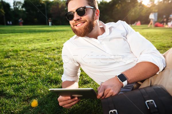 Feliz barbudo homem óculos de sol grama ao ar livre Foto stock © deandrobot