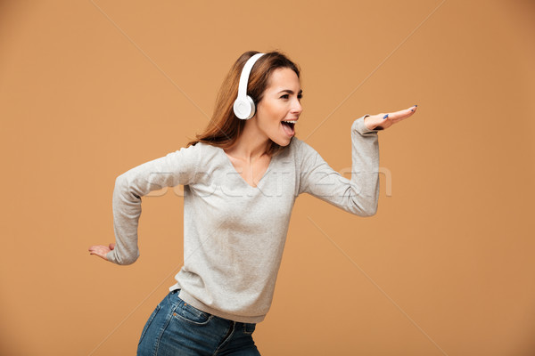 Emotional caucasian lady dancing isolated listening music Stock photo © deandrobot