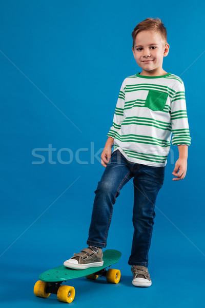Full length image of smiling young boy posing with skateboard Stock photo © deandrobot