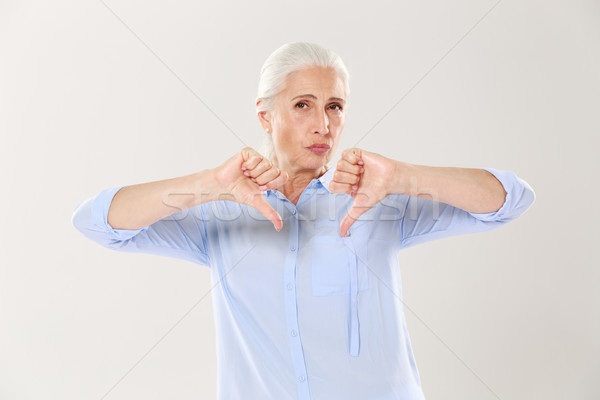 Displeased serious old woman showing thumb down and looking at t Stock photo © deandrobot