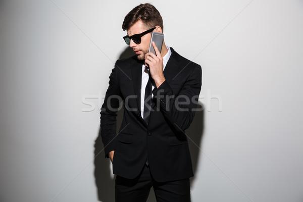 Zakenman zwart pak zonnebril praten mobiele telefoon geïsoleerd Stockfoto © deandrobot