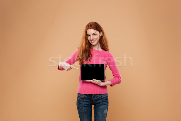Portrait of a cheerful pretty redhead girl pointing finger Stock photo © deandrobot