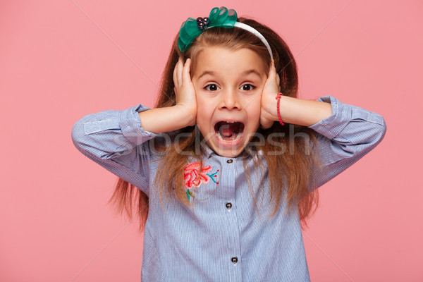 Surprised little girl covering her ears with both hands not list Stock photo © deandrobot