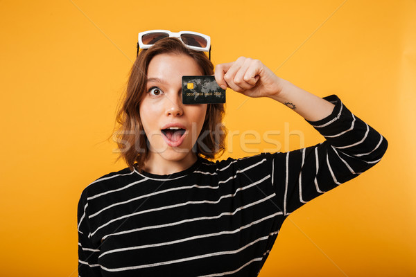 Portrait of a girl holding credit card at her face Stock photo © deandrobot