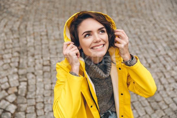 Caucasian cute female in yellow coat wearing hood on looking upw Stock photo © deandrobot