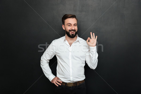 Adult guy in office posing on camera, smiling and gesturing with Stock photo © deandrobot