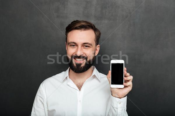 Caucasian brunette man showing smartphone on camera demonstratin Stock photo © deandrobot