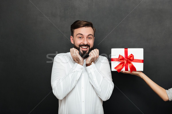 Portrait of excited brunette man rejoicing to get white gift box Stock photo © deandrobot