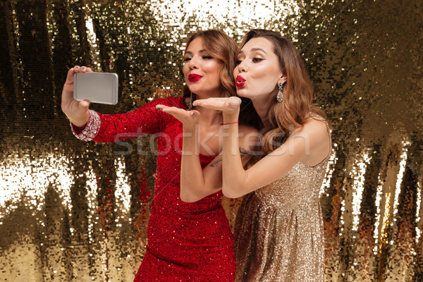 Portrait of two pretty smiling women in sparkly dresses Stock photo © deandrobot