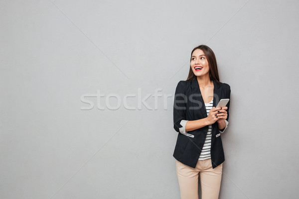 Cheerful asian business woman holding smartphone and looking away Stock photo © deandrobot