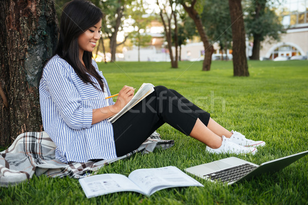 Cheerful asian female student in striped shirt, writing in noteb Stock photo © deandrobot