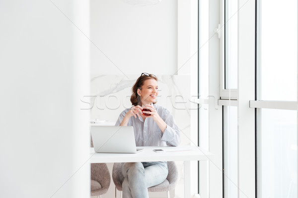 Young attractive brunette woman holding cup of tea while sitting Stock photo © deandrobot