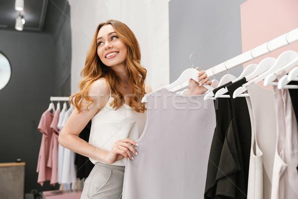 örömteli fiatal nő választ ruha ruházat bolt Stock fotó © deandrobot