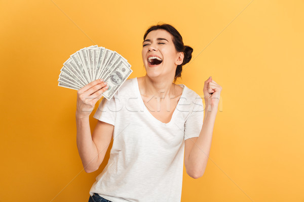 érzelmes fiatal csinos nő tart pénz gyártmány Stock fotó © deandrobot