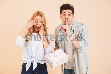 Image of surprised woman shouting in happiness while handsome ma Stock photo © deandrobot