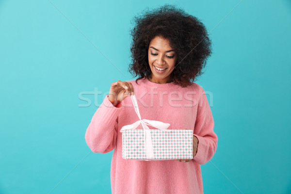 Portrait of american woman 20s with afro hairdo unwrapping gift  Stock photo © deandrobot