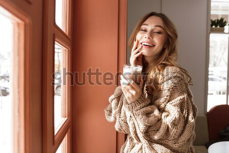 Photo of european woman 20s with brown hair talking on smartphon Stock photo © deandrobot