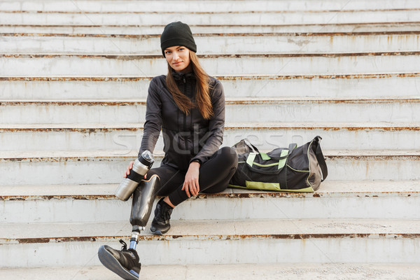 Photo of smiling handicapped woman in sportswear with prosthetic Stock photo © deandrobot