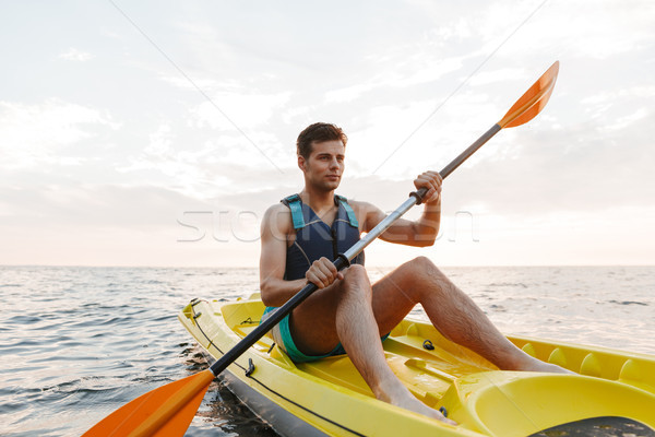 Handsome man kayaking on lake sea in boat. Stock photo © deandrobot