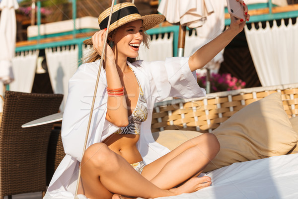 Photo of adorable woman 20s in straw hat smiling and taking self Stock photo © deandrobot