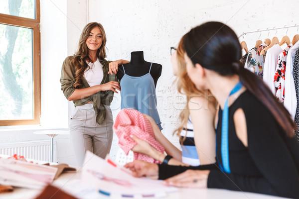 Mosolyog fiatal nő ruházat designer tanít kollégák Stock fotó © deandrobot