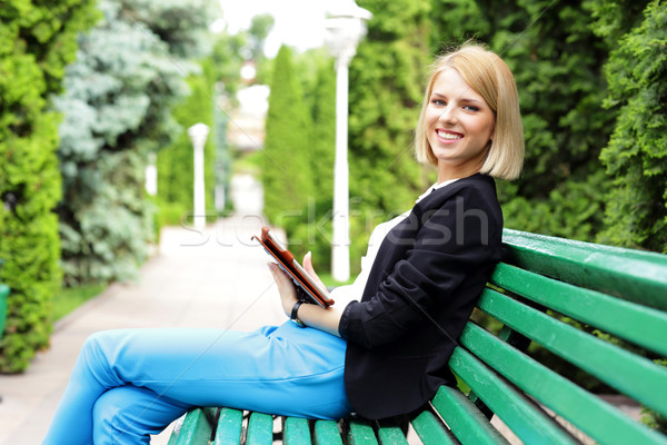 Happy woman sitting on the bench with tablet computer Stock photo © deandrobot