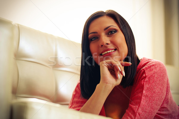 Portrait of a middle-aged smiling woman lying on the sofa Stock photo © deandrobot