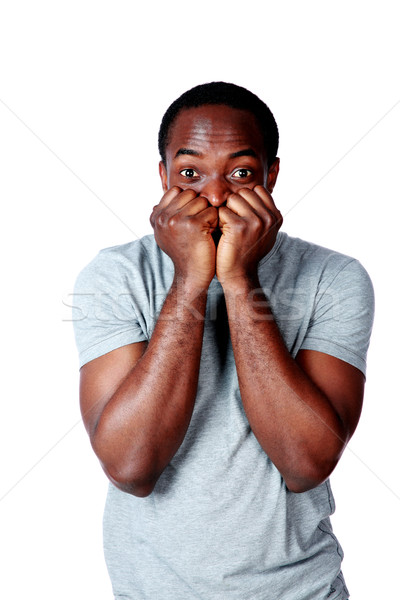 Portrait of a nerveous african man over white background Stock photo © deandrobot