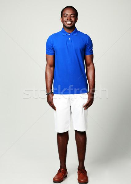 Tam uzunlukta portre gülen Afrika adam gri Stok fotoğraf © deandrobot