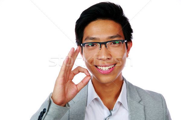 Happy asian man showing okay sign isolated on white background Stock photo © deandrobot